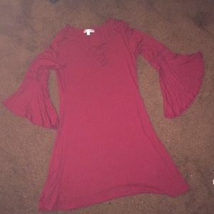 A red dress that is half sleeved flared sleeves .